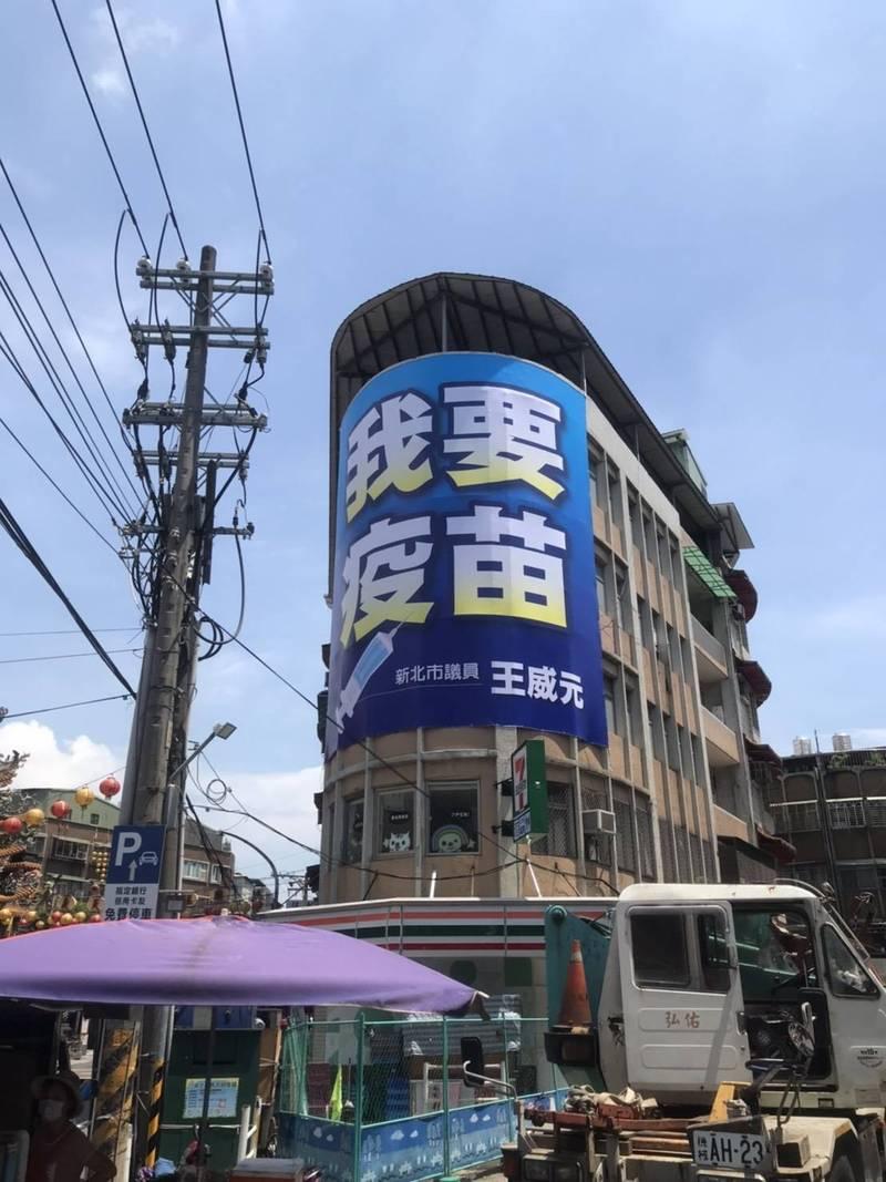 新北市議員王威元在路口高掛「我要疫苗」看板。(市議員王威元辦公室提供)