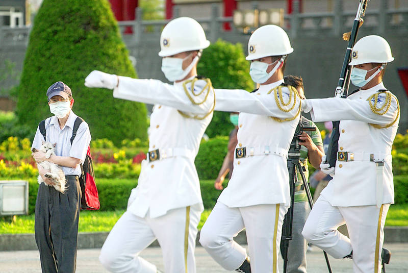A man holds a cat as ceremonial guards march past during the changing of the guard at the Chiang Kai-shek Memorial Hall in Taipei yesterday. Photo: CNA