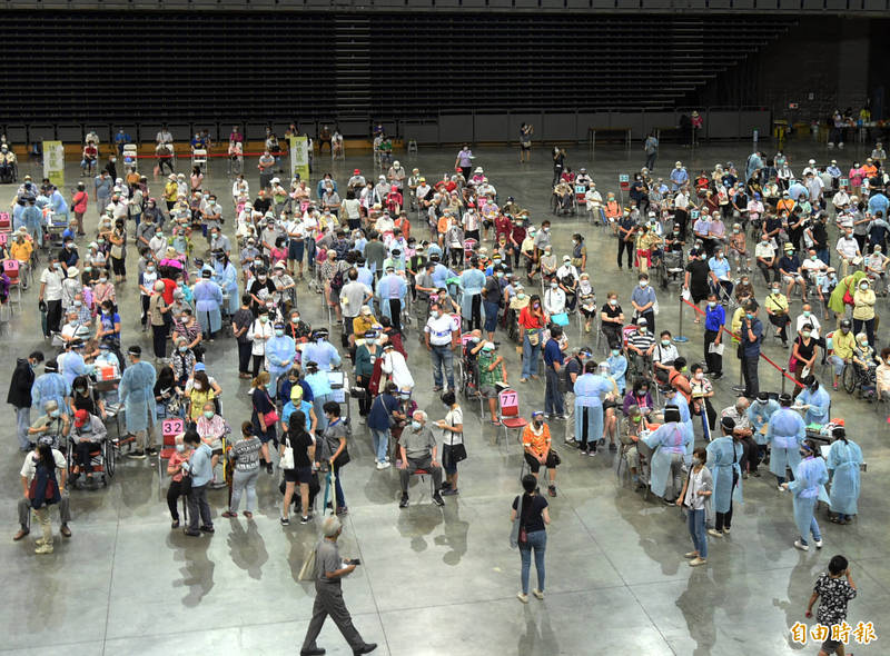 高雄巨蛋現場安排比照日本「宇美町」式施打法,就是讓長者排排坐好,由醫護滑動過去逐一施打。(記者張忠義攝)
