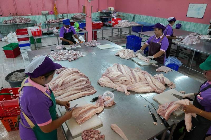 香港一名少女感染武漢肺炎確診,衛生當局今天公布,少女家中有冷藏的「泰國急凍鱷魚肉」呈現病毒陽性。圖為泰國曼谷屠宰場工人處理鱷魚肉。(路透)
