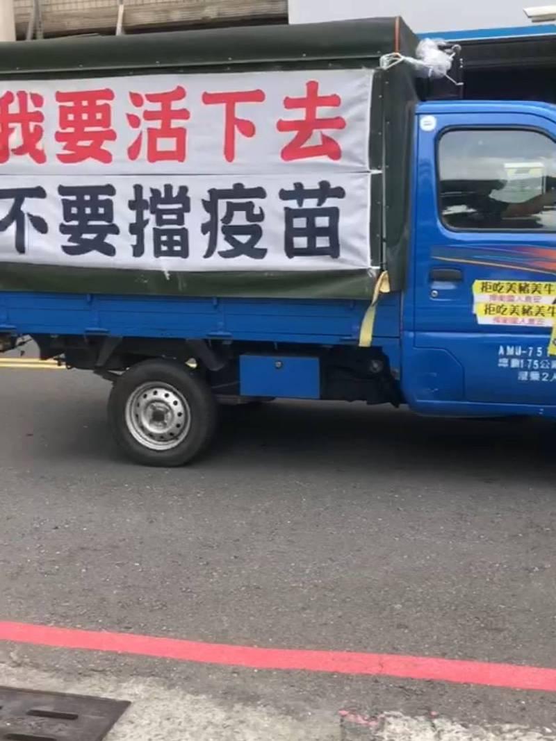 一輛小貨車懸掛「我要活下去」、「不要擋疫苗」白布條,繞行高雄市政府四周,連續鳴按喇叭妨礙安寧遭警攔查開單。(讀者提供)