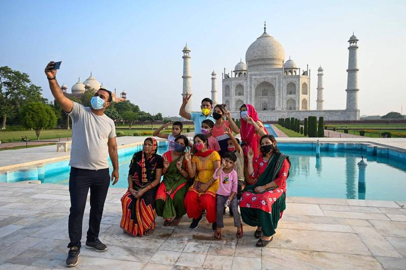 印度疫情趨緩,當局鬆綁防疫限制,觀光勝地泰姬瑪哈陵(Taj Mahal)今天重新開放,一群遊客在泰姬瑪哈陵拍照留念。(法新社)