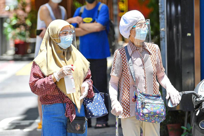 Two women wearing head coverings, masks, face shields, long sleeves and gloves walk down a street in Taipei yesterday, as the temperature rose well above 30°C. Photo: CNA