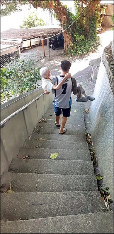 劉姓孝孫抱阿公走斜坡去打疫苗,被鄰居稱讚是「人世間最美風景」。(張哲源提供)