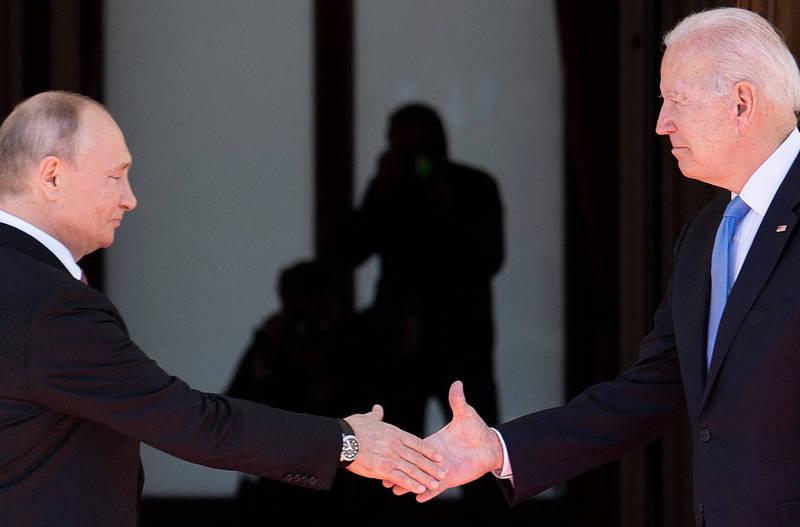 拜登(右)與普廷(左)16日在瑞士日內瓦舉行峰會,兩人抵達峰會會場握手致意。(法新社)