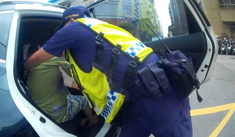 彭姓婦人外出因電動輪椅故障,員警熱心將她抱上巡邏車送返家。(記者何宗翰翻攝)