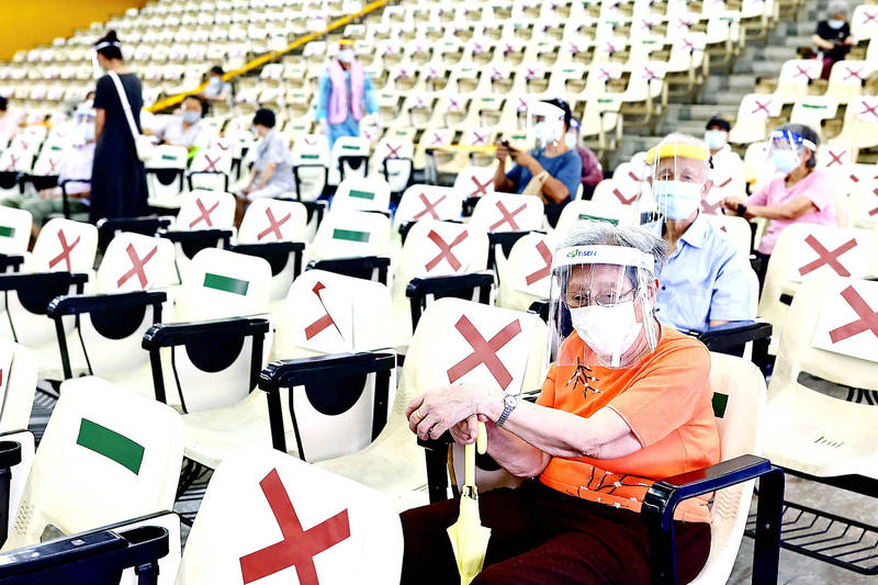 People sit in an observation area after being inoculated against COVID-19 at an auditorium in New Taipei City on Wednesday. Photo: Ann Wang, Reuters