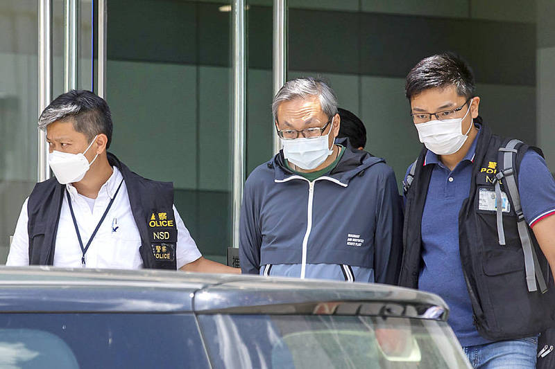 Next Digital Ltd chief executive officer and Apple Daily publisher Cheung Kim-hung, center, is escorted from the newpaper's offices by Hong Kong National Security Department officers in Hong Kong yesterday. Photo: Bloomberg