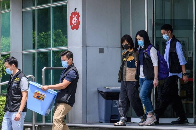 香港警方今早包圍蘋果日報社大舉搜索,並押走蘋果日報副社長陳沛敏(右三)等報社高層。(法新社)