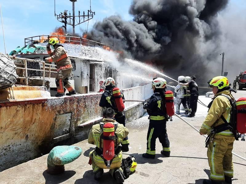基隆市正濱漁港內「凱勝23號」漁船今天上午10時許發生火燒船意外。基隆市消防局獲報馳援,出動8輛水箱車前往灌救,海巡署基隆海巡隊也緊急出航,在海上灌救中。(記者林嘉東翻攝)