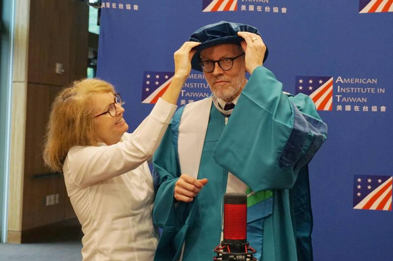 美國在台協會台北辦事處長酈英傑(右),由妻子布蘭達為其穿戴中山大學「台灣青」的博士學位袍、都鐸帽,獲頒名譽社會科學博士學位。(AIT提供)