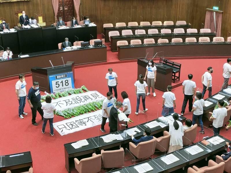 國民黨立委在議場台前獻上白菊花,白布條寫著「來不及說再見,只因等不到疫苗」。(立法院國民黨團提供)