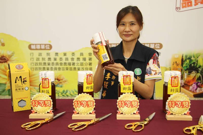 新竹縣農會總幹事李筱華說今年從44點選出4點特等獎的優質國產龍眼蜜,未來上市一樣會有如她手中的生產追溯QR Code供消費者查詢其生產紀錄。(記者黃美珠攝)