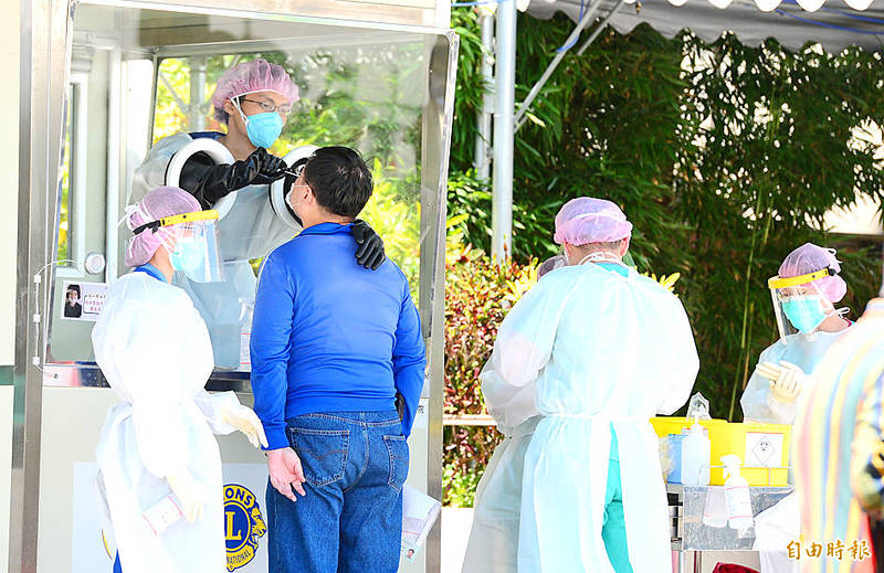 New Taipei City Hospital staff administer a rapid screening test at the hospital's branch in Sanchong District yesterday. Photo: Wang Yi-sung, Taipei Times