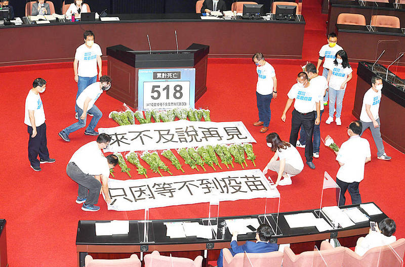 Chinese Nationalist Party (KMT) legislators yesterday lay banners next to bouquets of white chrysanthemums on the legislative floor in Taipei to commemorate those who have died during the COVID-19 pandemic. Photo: CNA