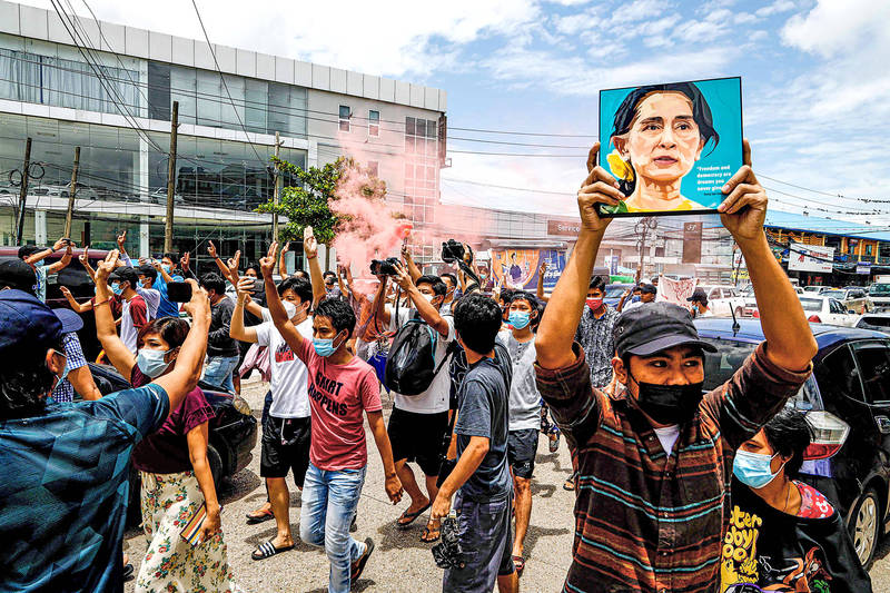 A protester holds up a painting of Aung San Suu Kyi to mark her birthday during a demonstration against the military coup in Yangon, Myanmar, yesterday. Photo: AFP