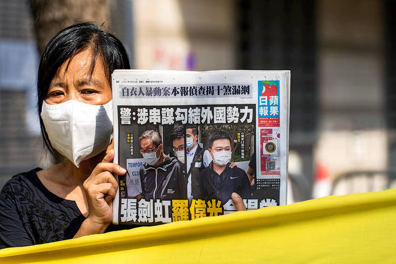 A supporter holds a copy of the Apple Daily newspaper ahead of a court appearance by Next Digital Ltd chief executive officer Cheung Kim-hung and Apple Daily editor-in-chief Ryan Law at the West Kowloon Magistrates' Courts in Hong Kong yesterday. Photo: Bloomberg