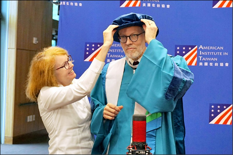 Li Yingjie (right), Director of AIT, was awarded an honorary doctorate in social sciences by his wife Brenda wearing a doctorate gown and tudor hat from Sun Yat-sen University.  (Provided by AIT)