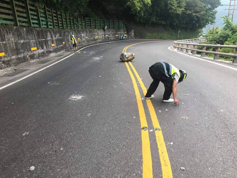 事發後,工作人員清除路面落石。(記者江志雄翻攝)