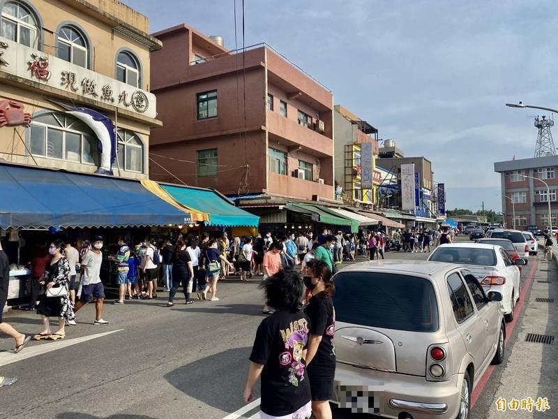 桃園市大園區的竹圍漁港魚貨大樓周邊出現採買人潮,有民眾貪圖方便,索性將車輛違停在紅線上。(記者魏瑾筠攝)