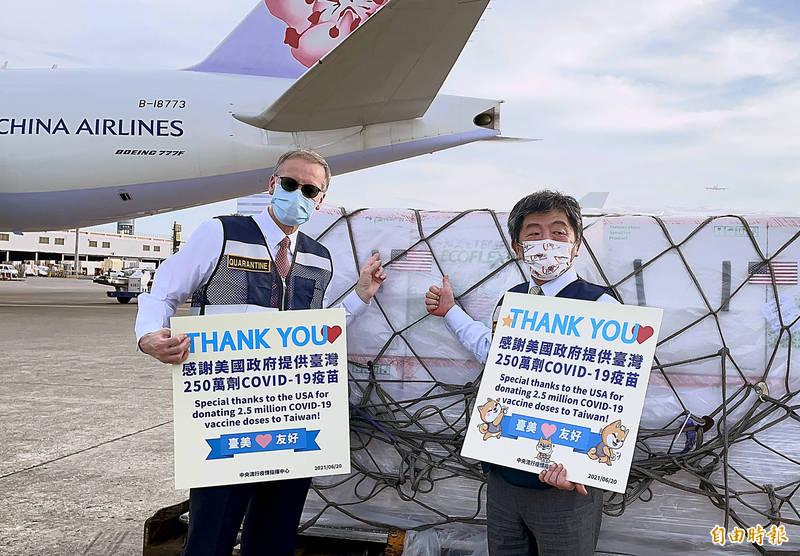 美國政府援助台灣的250萬劑的莫德納疫苗20日下午4時30分運抵桃園機場,中央流行疫情中心指揮官陳時中(左)、美國在台協會(AIT)台北辦事處長酈英傑(右)前往桃園機場接機並關切卸載及後送作業。兩人也在疫苗旁舉起寫上「感謝美國政府提供台灣250萬劑COVIN-19疫苗」的手牌合影,突顯台美同心協力共同對抗這一次的疫情友好關係。(記者朱沛雄攝)