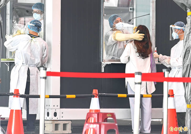 Medical personnel work at a COVID-19 testing station in New Taipei City's Banciao District yesterday. Photo: Chen Chih-chu, Taipei Times