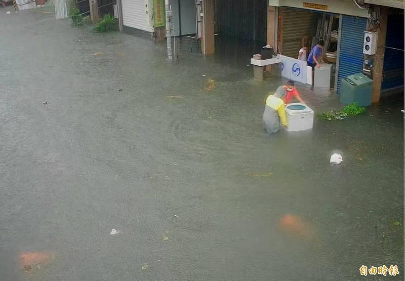 圖為彰化員林市東山里山腳路大淹水,有民宅家洗衣機遭大水沖走,民眾趕緊搶救。(記者陳冠備攝)