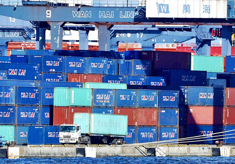 A cargo truck drives past containers at the Port of Kaohsiung on June 8. Photo: CNA