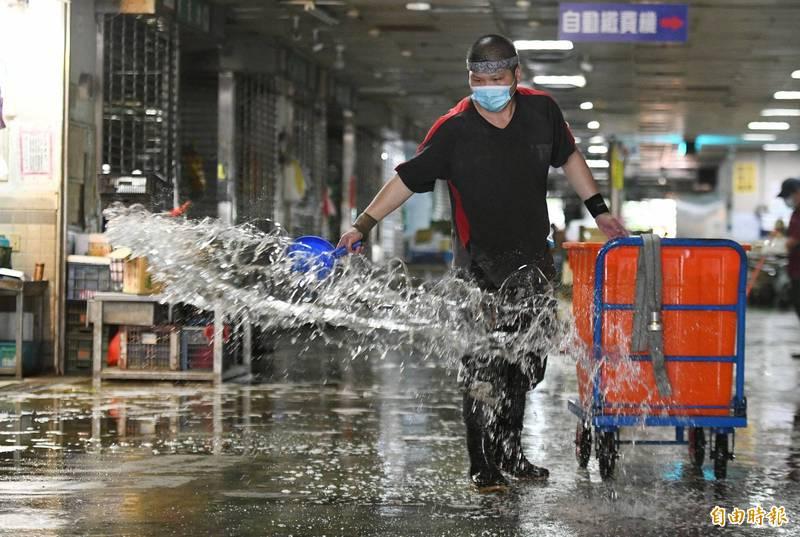 北農截至目前已有45人確診,台北市府21日啟動防疫專車將第二果菜批發市場100多人分批送往和平醫院快篩,市場工作人員也利用休市這一天清洗地板。(記者廖振輝攝)