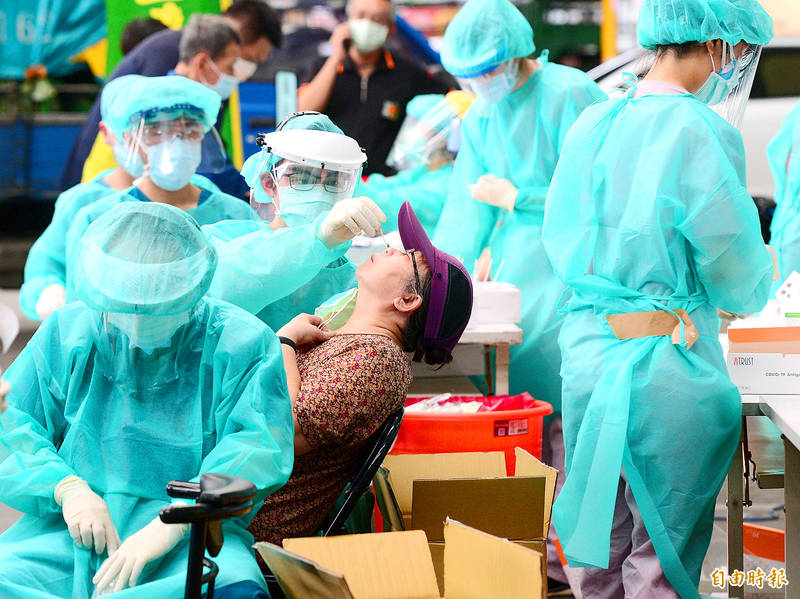Vendors receive COVID-19 tests at a rapid testing station at New Taipei City Sanchong Fruit and Vegetable Market yesterday after a cluster infection broke out at Taipei Agricultural Products Marketing Co. Photo: Wang Yi-sung, Taipei Times