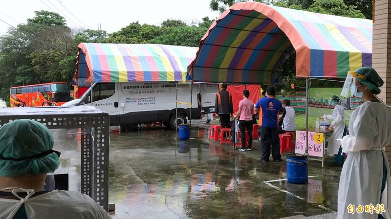 南投市漳和里集會所社區篩檢活動,民眾在雨中排隊等候情形。(記者謝介裕攝)