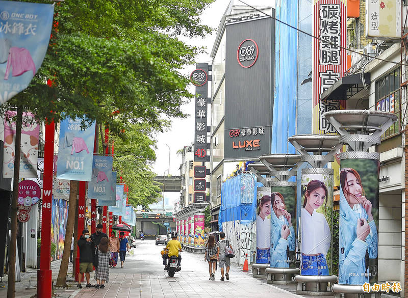 People in Taipei's Wanhua District yesterday walk past in89 Deluxe Digital Cinema, which is temporarily closed amid a level 3 COVID-19 alert. Photo: Chen Chih-chu, Taipei Times