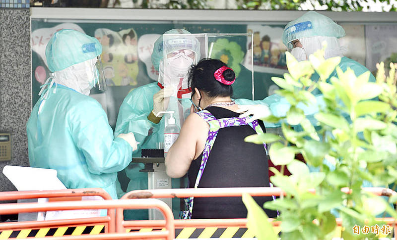 Healthcare workers at a temporary test station at Taipei Municipal Wanda Elementary School in Wanhua District yesterday conduct a COVID-19 test on a vendor from the First Fruit and Vegetable Wholesale Market. Photo: Peter Lo, Taipei Times