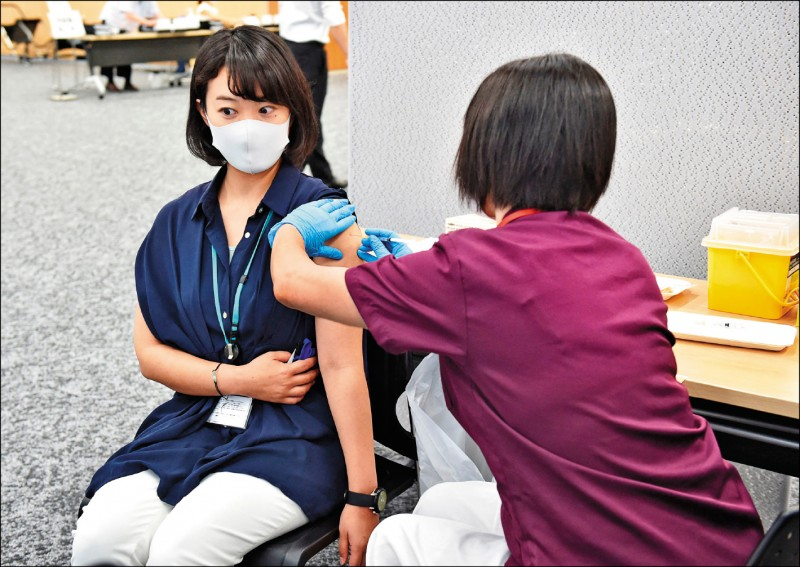 圖為東京三得利株式會社員工二十一日在辦公室接種疫苗。(法新社)