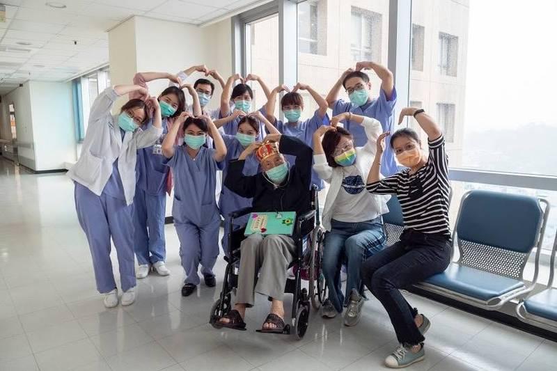 102歲張爺爺(前中)染疫康復出院,醫護人員同歡。(雙和醫院提供)