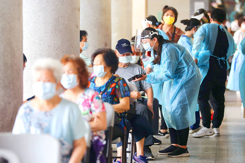 Taipei Medical University Hospital staff vaccinate people at an inoculation station at the city's Xinyi High School yesterday. Photo: CNA