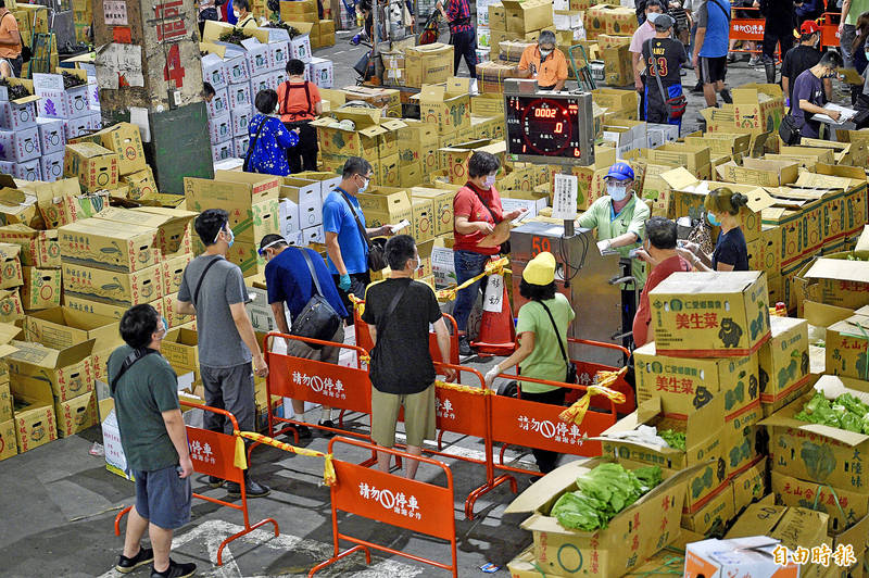 Vendors surround an auction podium at the Taipei First Wholesale Fruit and Vegetable Market yesterday. Photo: Lo Pei-der, Taipei Times