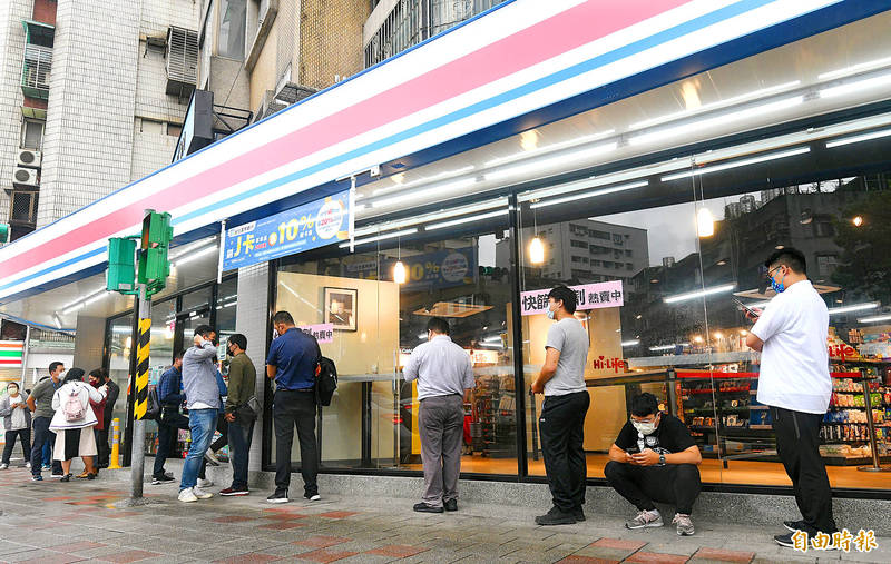 People wait outside a convenience store to purchase COVID-19 home test kits in Taipei yesterday. Photo: Liao Chen-huei, Taipei Times