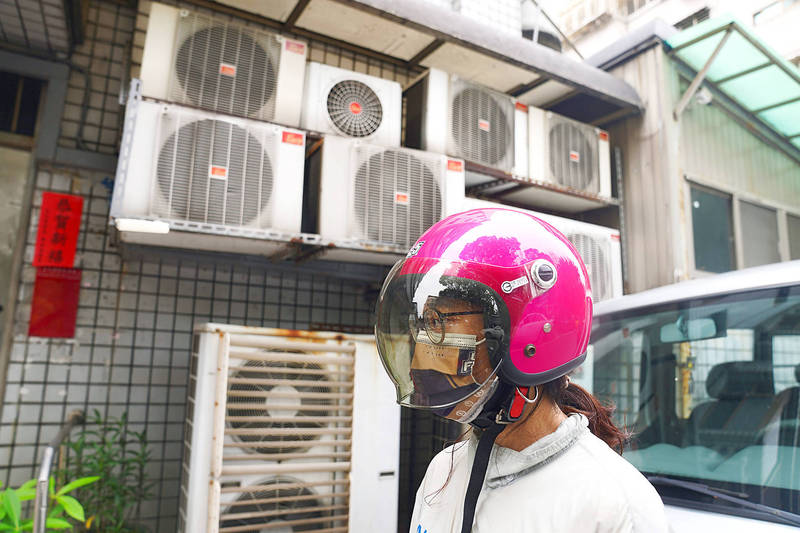 A woman wearing a mask and motorcycle helmet walks past air-conditioner units outside a building in Taipei on May 22. Photo: CNA