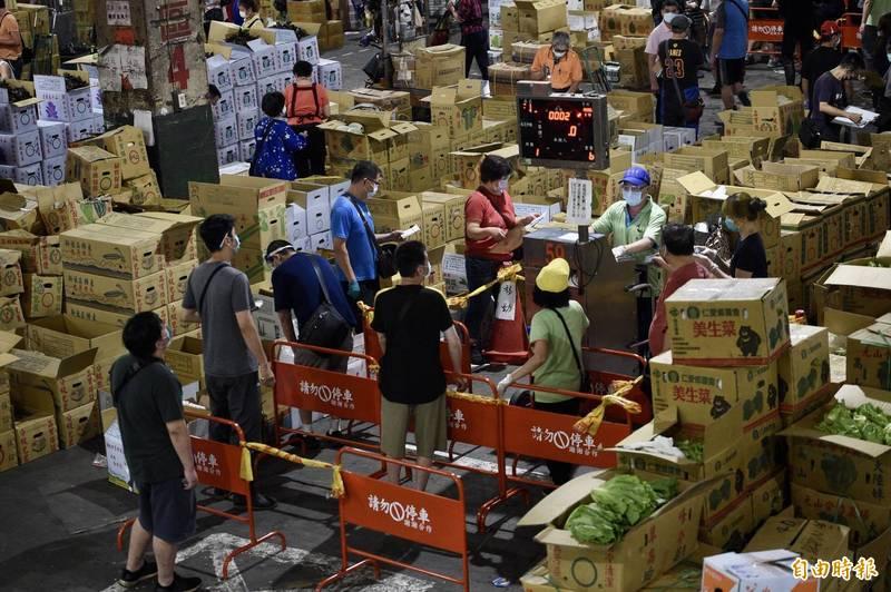北農爆發群聚感染,市府及各單位積極防堵。圖為台北第一果菜市場24日交易情形。(記者羅沛德攝)