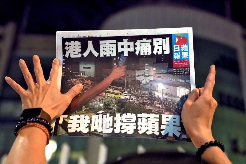 香港蘋果日報廿四日出版最後一份實體報紙,民眾在凌晨買到後比出「五大訴求,缺一不可」手勢。(路透)