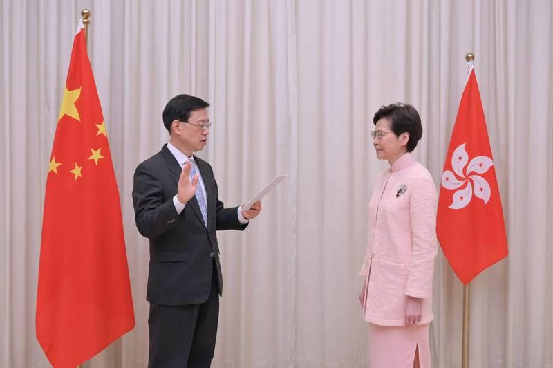 中國國務院昨頒布人事任命,確認香港保安局長李家超(左)升任政務司司長。圖為李家超宣誓就職畫面。(路透)