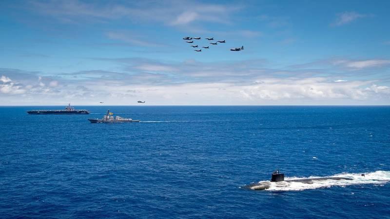 6月22 日,卡爾文森號航空母艦(圖左)、驅逐艦杜威號(中)和攻擊型潛艦海狼號(圖右)在夏威夷群島作戰區域聯合演練,艦載戰機攻擊中隊和空中加油中隊飛越艦隊上空。(翻攝自美國太平洋艦隊官網)
