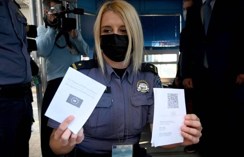 歐洲聯盟今天宣布啟用數位疫苗證明。圖為一名女警展示乘客的疫苗護照。(歐新社)