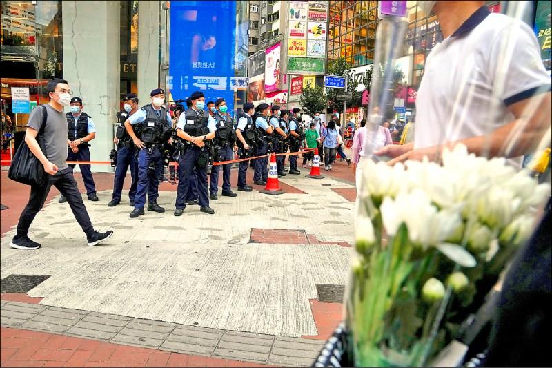 香港民眾持鮮花前往銅鑼灣悼念梁健輝,但大批警方在四周戒備截查。(美聯社)