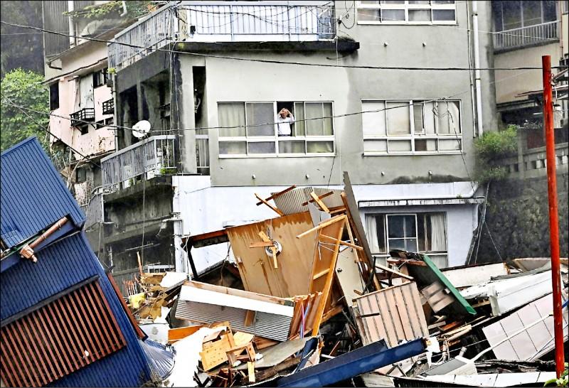 當地居民事後隔窗眺望滿目瘡痍的受災現場。(路透)
