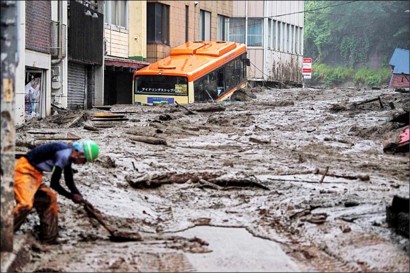 日本靜岡縣熱海市伊豆山地區豪雨成災,大量土石流沖向民宅,淹沒道路與建築,就連公車也受困泥濘中動彈不得。(法新社)