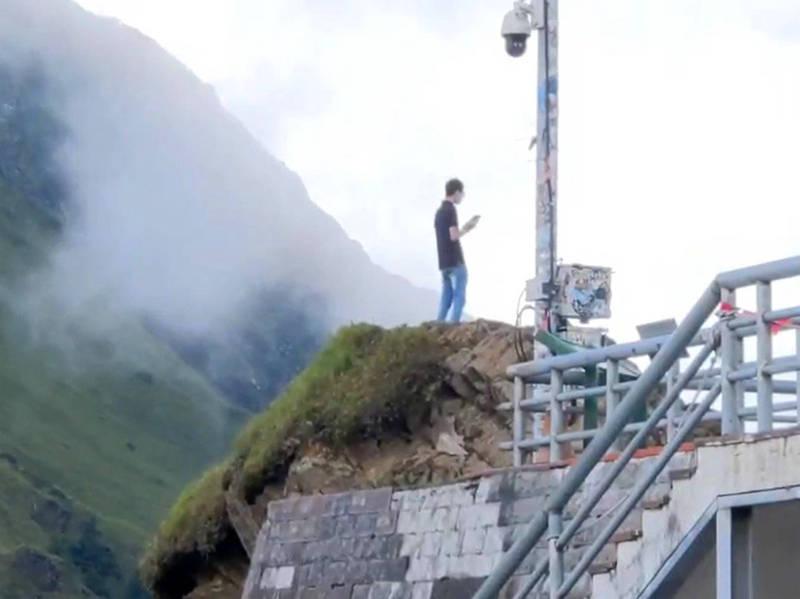 年輕遊客冒險攀爬岩石到武嶺亭旁的地方拍照。(民眾提供)