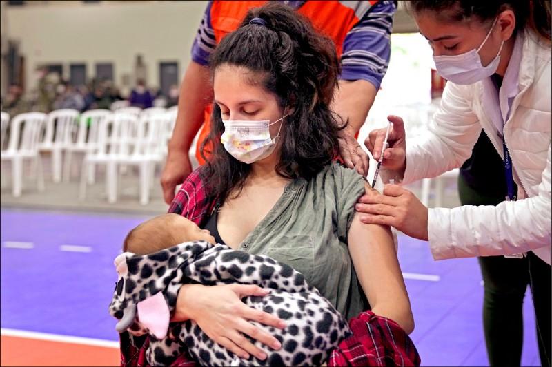 巴拉圭一名母親三日在首都亞松森疫苗接種站打俄羅斯「史普尼克V」疫苗,同時以母乳哺育一個月大新生兒。(美聯社)