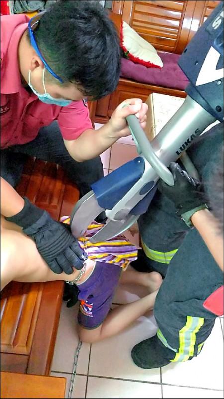 消防人員以油壓剪剪斷鐵鍊協助男童脫困。為保護兒童圖經特殊處理。 (民眾提供)